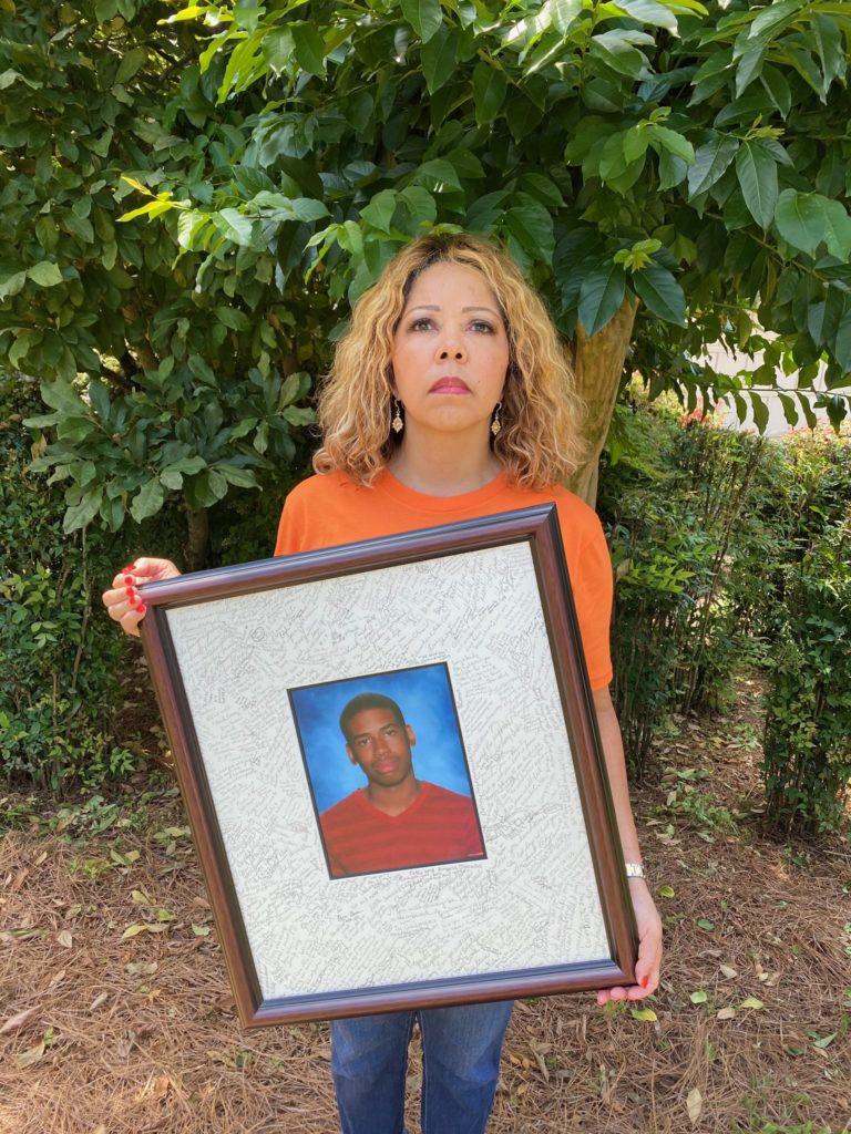 Georgia Representative Lucy McBath wear an orange shirt while holding up a photo of her son Jordan